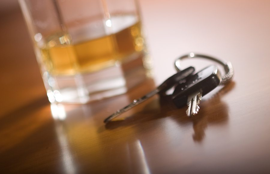 car keys and glass of liquor on brown wooden table