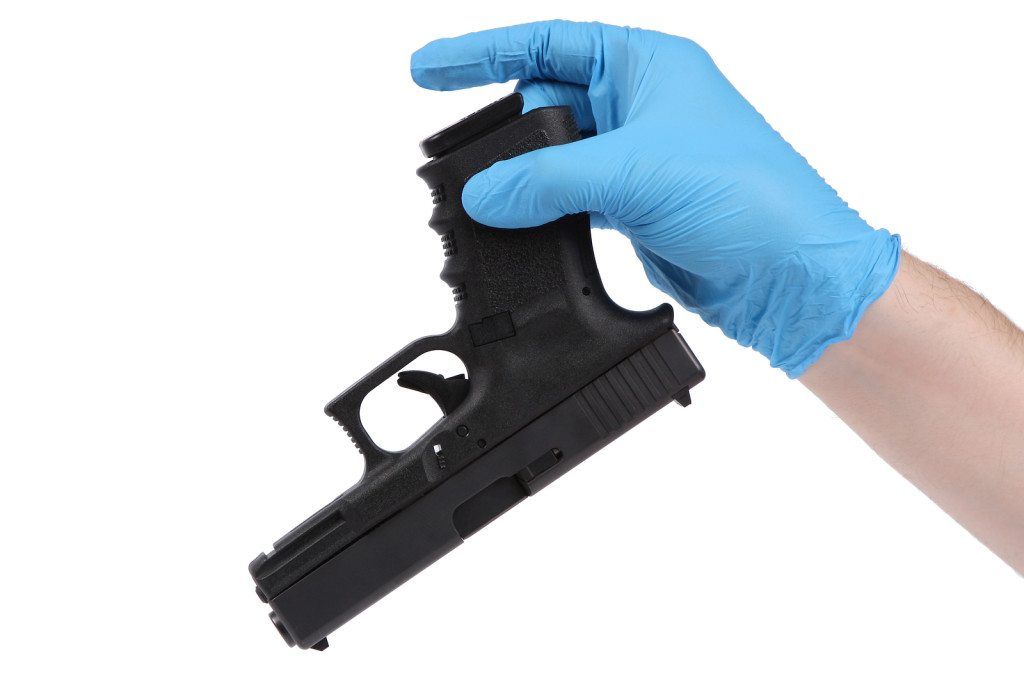 man wearing blue latex glove holds up gun as evidence