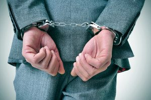 a man wearing a suit with his wrists handcuffed in the back