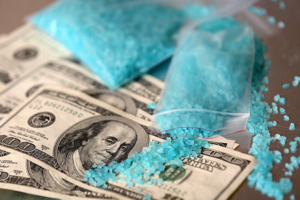 Drug laboratory: blue methamphetamine and money on table close u